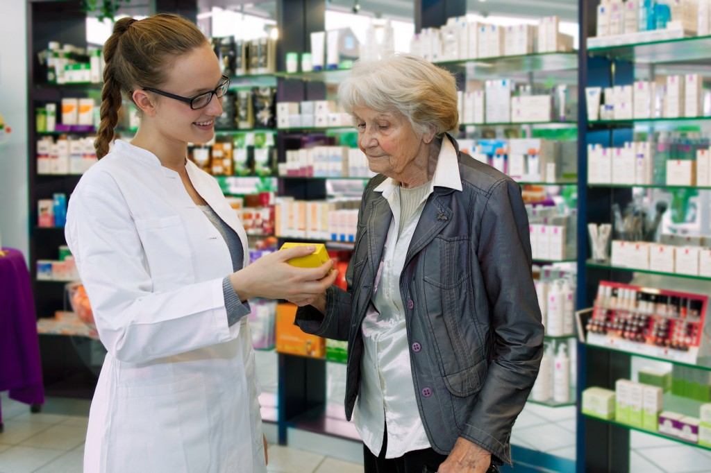 Pharmacist advising medication to senior patient.