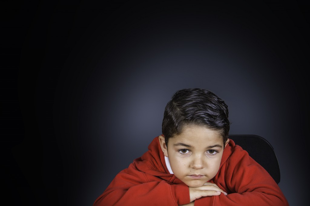 A portrait of a young boy wearing a red hoodie laying his head down